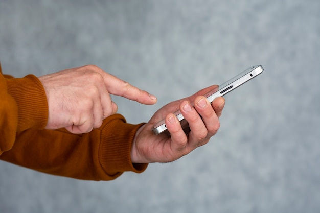 갈색 재킷을 입은 남자가 손에 스마트폰을 들고 손가락으로 누릅니다.