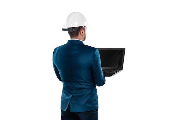 ビジネススーツを着た男、頭に白いヘルメットをかぶった建築家