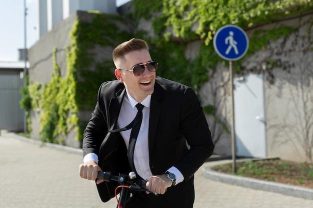 Мужчина в деловом костюме и солнечных очках катается на электросамокате и смеется
