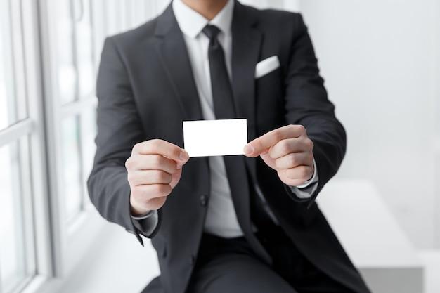 명함 모형을 들고 비즈니스 정장을 입은 남자.