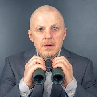 비즈니스 정장에 남자는 쌍안경을 통해 보인다. 성공적인 비즈니스의 목표.