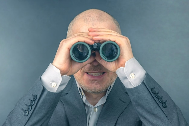 ビジネススーツを着た男性が双眼鏡で見ています。成功するビジネスの目標。