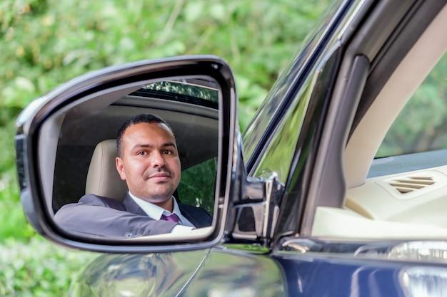 車のホイールの後ろに座っているビジネススーツの男がバックミラーを見る