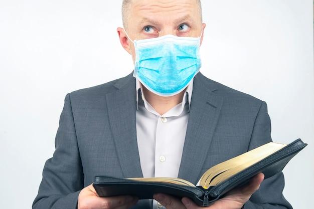 그의 얼굴에 의료 마스크와 비즈니스 정장에 남자는 성경을 공부하고 있습니다.