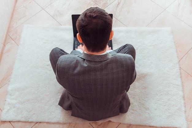 家庭環境でラップトップを使用して作業するビジネススーツの男