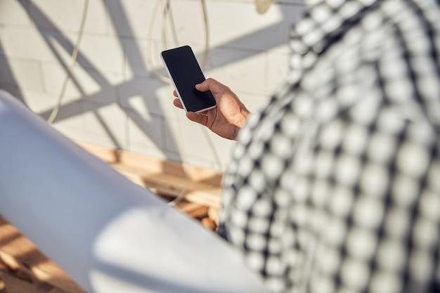スマートフォンを使用して紙を運ぶチェックシャツを着た男