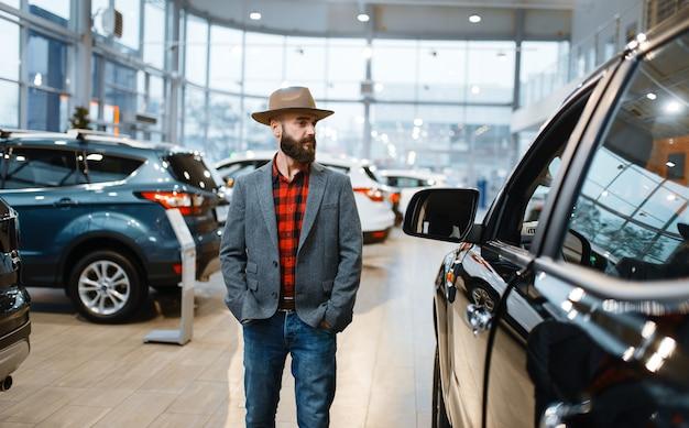 自動車販売店で新しい自動車を選ぶカウボーイハットの男。