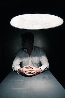 얼굴이 보이지 않는 램프에서 나오는 빛으로만 밝혀진 어두운 방에 있는 남자
