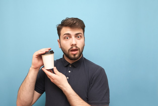 暗いシャツとひげの男、彼の手でコーヒーの紙コップを持って感情的な顔で青に