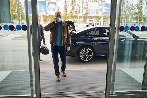 彼のプライベートドライバーが続くフェイスマスクの男