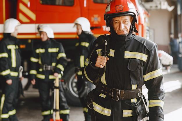 Человек в пожарной форме. пожарный возле машины. человек в гараже