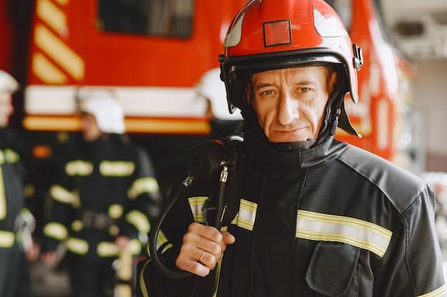 불 제복을 입은 남자. 자동차 근처 소방 관. 차고에있는 남자