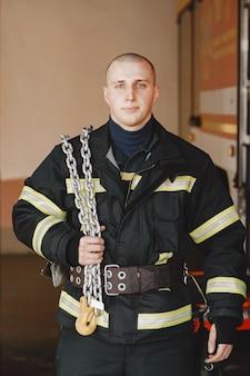 火の制服を着た男。車の近くの消防士。ガレージの男