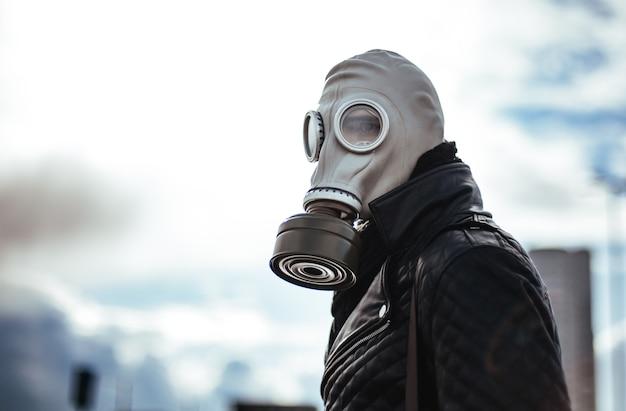 空の街の通りに立っている防毒マスクの男。
