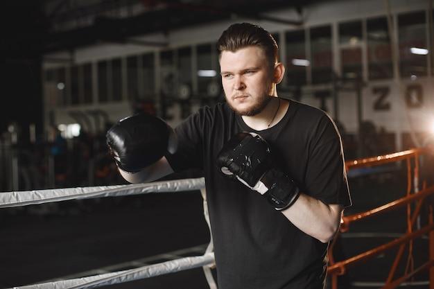 手袋をはめた男。スポーツ服のボクサー。あごひげを生やした男。