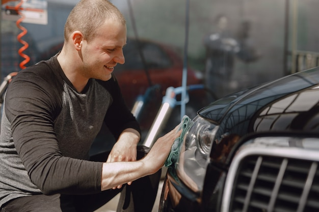 Мужчина в сером свитере вытирает машину в автомойке