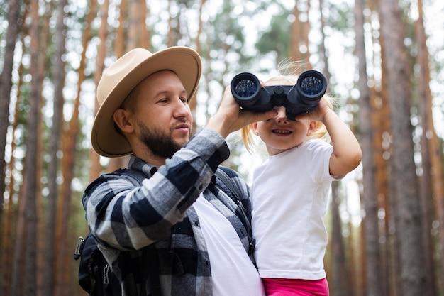 모자를 쓴 남자와 배낭, 아이가 쌍안경을 통해 숲을 하이킹하는 동안 바라본다. 산이나 숲으로 가족 하이킹.