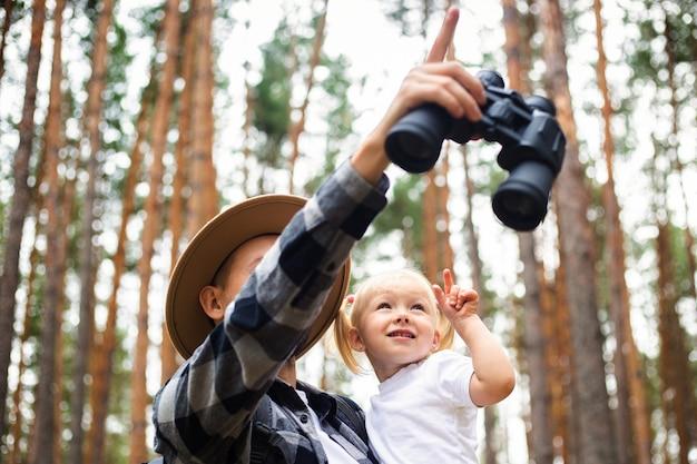 森でのハイキング中に帽子をかぶった男と子供。山や森への家族のハイキング。