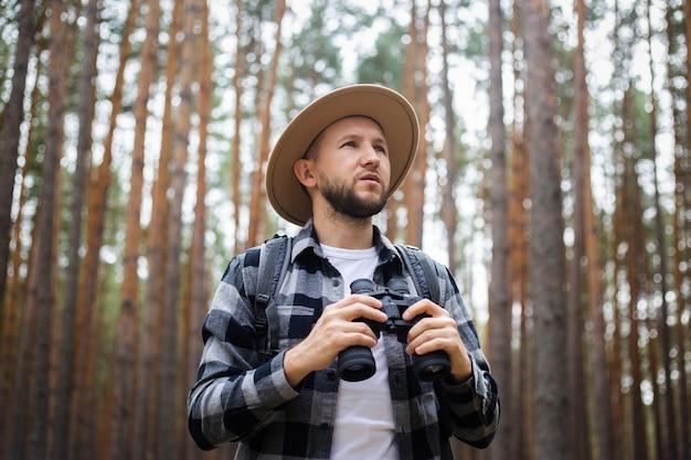 모자와 격자 무늬 셔츠를 입은 남자가 쌍안경을 들고 숲을 걷는다.