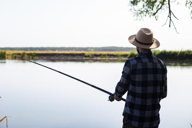 모자와 격자 무늬 셔츠를 입은 남자가 강가에서 낚시를하고 있습니다.