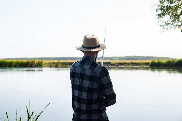 帽子と格子縞のシャツを着た男が川のほとりで釣りをしている。