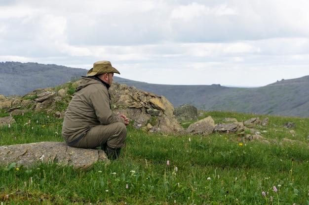 모자와 여행복을 입은 남자는 황량한 산 풍경의 돌 위에 앉아 있다