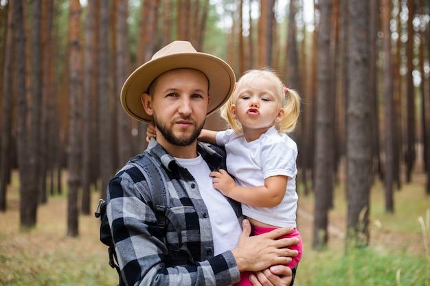 帽子をかぶった男が森の中を歩いている間、子供を腕に抱きます。山や森への家族のハイキング。