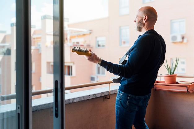 ひげと帽子をかぶった男が夏にバルコニーでギターを弾きます。