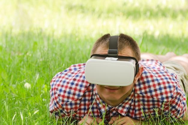 Человек в шлеме виртуальной реальности лежит на зеленой траве