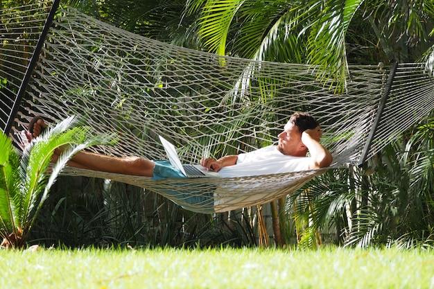 Человек в отеле летом с ноутбуком лежал в гамаке