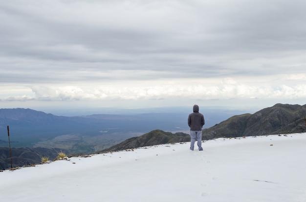 Мужчина в куртке стоит на вершине горы в природном заповеднике вильявисенсио в мендосе, аргентина