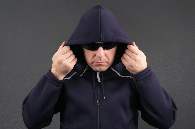 후드와 어두운 안경 재킷을 입은 남자