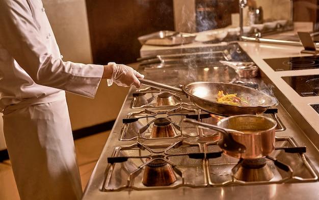 キッチンの男が炊飯器の中火でさまざまな色のコショウのスライスで熱い鍋を回します
