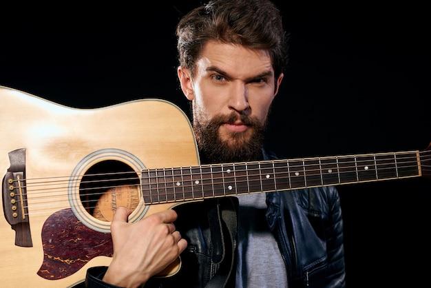 アコースティックギターと革のジャケットの男