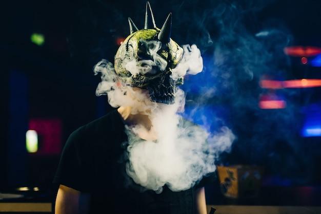 Мужчина в маске курит кальян и пускает облако дыма