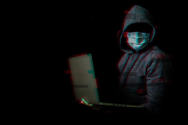 顔とフードのないマスクの男は、暗闇の中で彼の手でラップトップを保持します