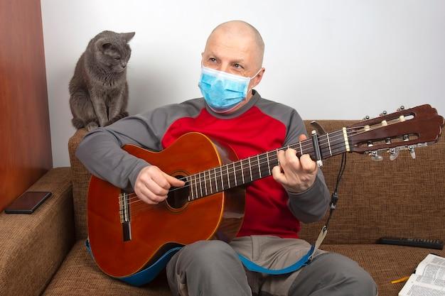 코로나 바이러스 전염병으로 인해 집에서 의료 마스크를 쓴 남자가 회색 고양이 옆에서 클래식 기타를 연주합니다.