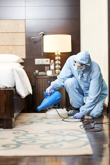 Мужчина в защитной одежде распыляет дезинфицирующие средства возле кровати в гостиничном номере. коронавирус и концепция карантина