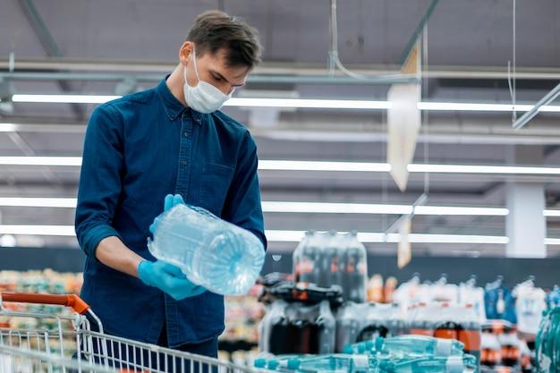 スーパーマーケットで水を買う保護マスクの男