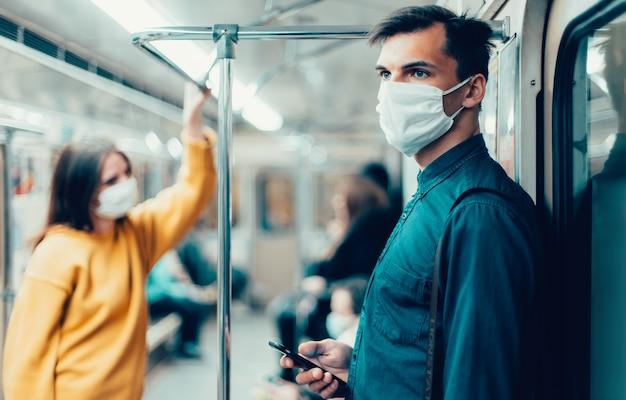 Человек в защитной маске смотрит на экран своего смартфона