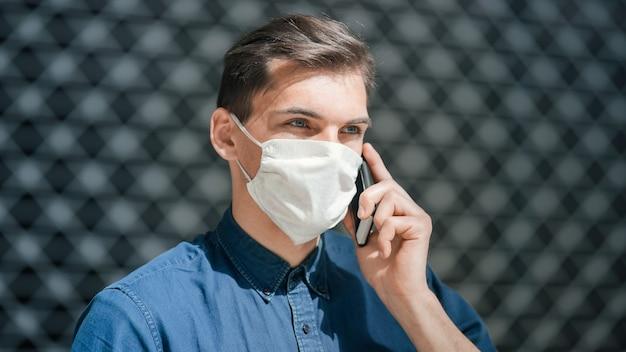 Человек в защитной маске разговаривает по смартфону