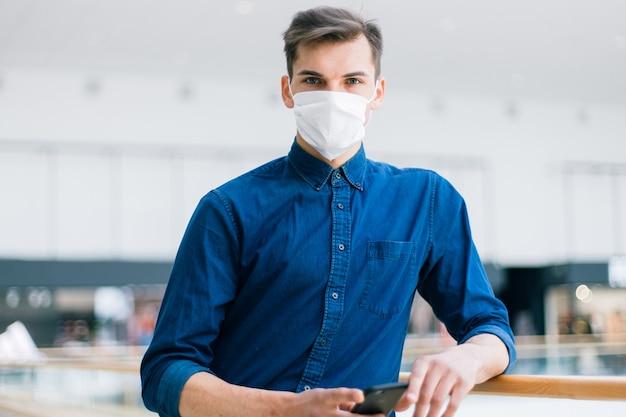 Человек в защитной маске со смартфоном стоит на улице