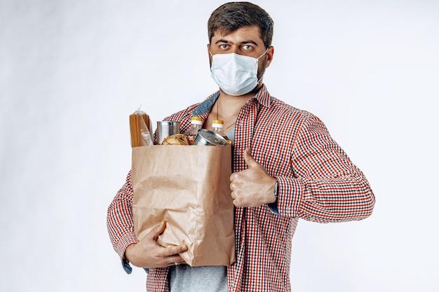 食料品店からのバッグを持った保護用医療マスクの男。食品デリバリー