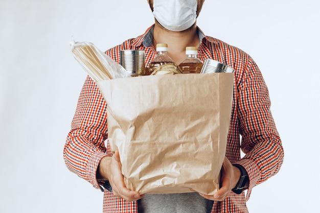 Человек в защитной медицинской маске с сумкой из продуктового магазина
