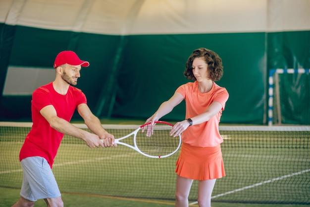 빨간 모자와 그의 여성 코치와 함께 운동을하는 라켓을 가진 남자