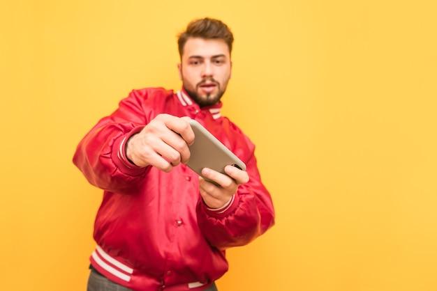 빨간 재킷과 수염을 입은 남자는 스마트 폰에서 비디오 게임을하는 데 집중합니다.