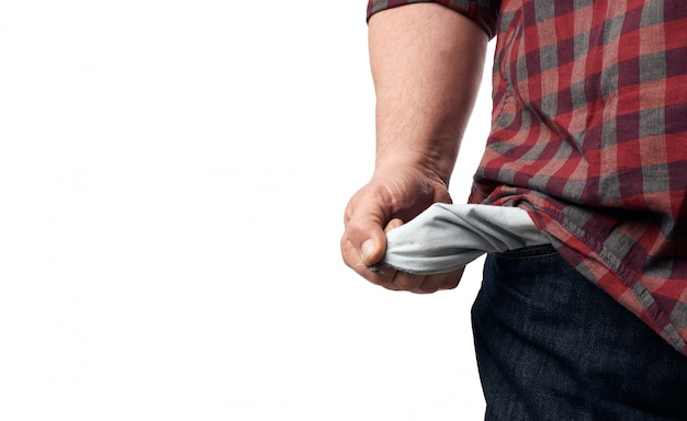 Человек в красной клетчатой рубашке вывернул пустые карманы штанов