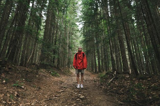 赤いレインコートを着た男が山の小道に立っている