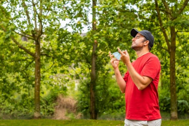 수술용 마스크를 벗고 코로나바이러스 전염병의 종식을 축하하는 빨간 셔츠를 입은 남자