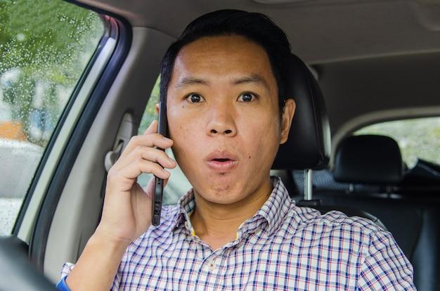 전화에 충격적인 표정으로 스카치 셔츠를 입은 남자